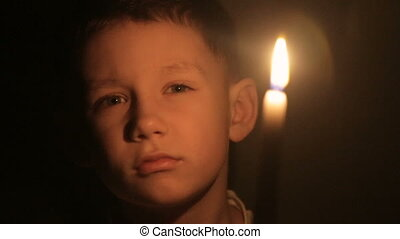 A child holds a burning candle in his hands