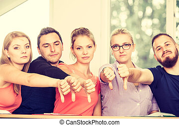 Sad group of students giving thumbs down
