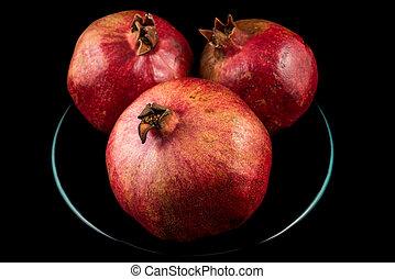 Pomegranates - Three pomegranates on plate with black...