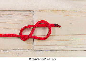 Figure-eight knot made with red rope on wooden background.