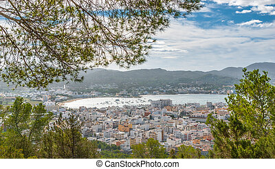 View through naturally framing trees into St Antoni de Portmany & surrounding area in Ibiza.  Clearing November day in the Islands near Spain.