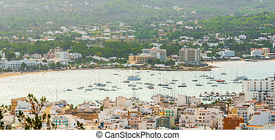 Marina with moored boats behind St Antoni de Portmany, Ibiza, on a clearing day in November.