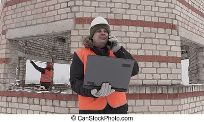 Construction engineer with laptop talking on smart phone...