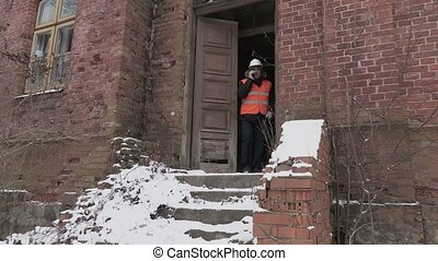 Building inspector talking on cell phone near old building