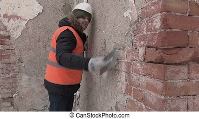 Builder using grinding tool and checking wall