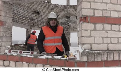 Construction engineer talking on smart phone and walking in unfinished building