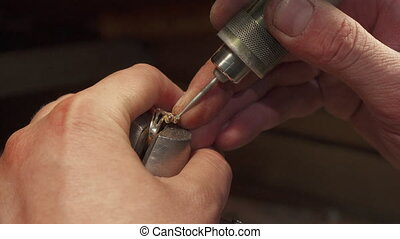 Man putting gemstone into the jewelry item - Caucasian man...