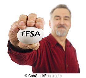 Mature man holds an egg with TFSA on it. TFSA is a tax free...
