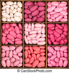 Wooden storage box filled with pink sugared almonds. -...