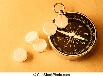 White aspirin pills and compass in closeup