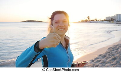 Young woman giving thumbs up hand sign on beach - happy...