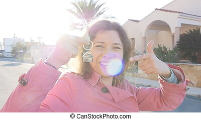 Young woman holds the keys to a new home. Property concept