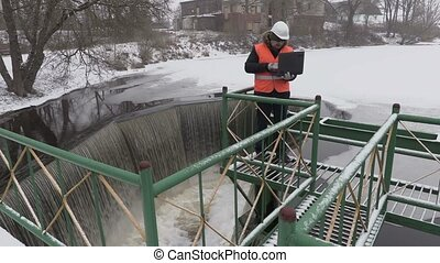 Engineer working with laptop near floodgate in winter