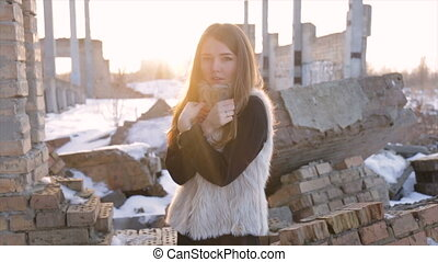 Girl in a sheepskin coat on a background of an abandoned building.slow motion