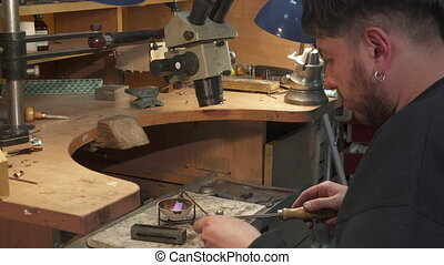 Jeweler direct the gas torch into the crucible - Bearded...