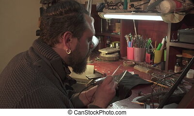 Man uses engraver tool - Bearded caucasian man using...