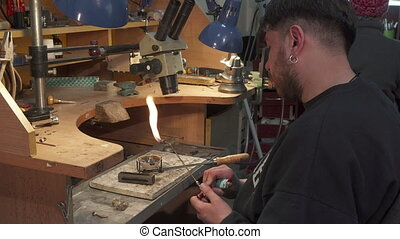 Jeweler sets fire on gas torch - Young caucasian jeweler...