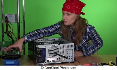 Professional technician girl installing new hard drive into...