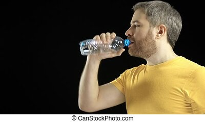 Handsome gray haired man in yellow tshirt drinking water...