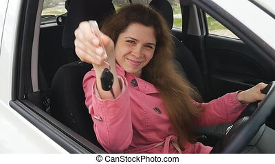Happy young woman driver holding car keys driving her new car