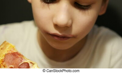 Cute boy eating pizza