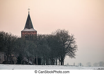Church and houses of a small village behind the dike -...