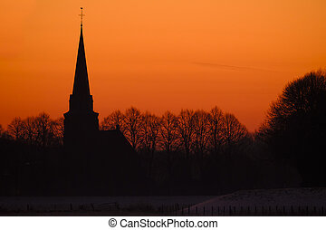 Silhouette of church against a sunset