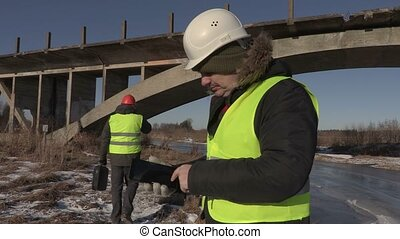 Engineer with tablet PC near the bridge