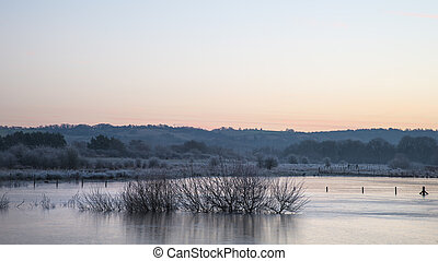 Beautiful vibrant English countryside lake image with frost...