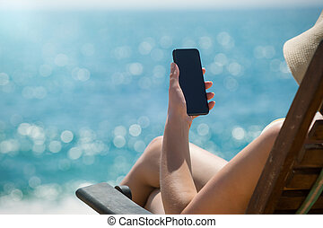 Young girl lying on a beach lounger with mobile phone in...