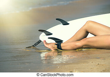 Young beautiful surfer girl on beach with surf board at day break