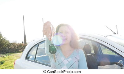 Happy young woman driver holding car keys driving her new...