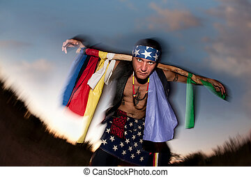 Indigenous man with ceremonial pole representing seven...