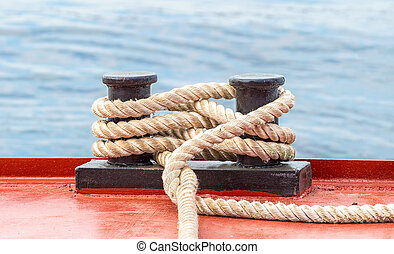 Mooring bollard with a fixed rope on the ship against the...
