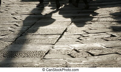 Silhouettes of people on the cobblestone pavement. -...