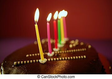 Colorful birthday light candles in chocolate cake - Colorful...