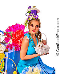Woman in easter style holding rabbit and flowers in basket....