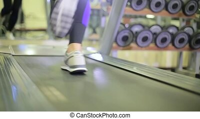 Girl on a treadmill in a fitness club.