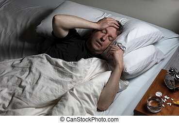 Mature man in physical pain while trying to fall asleep -...