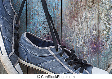 pair of old worn blue shoe hanging on a nail
