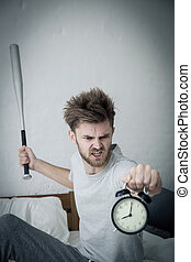 Portrait upset angry with baseball hit young man screaming at alarm clock on bedroom. Employee running late. Time management with business concept