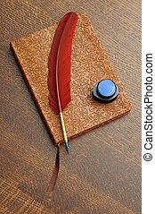 Journal with Feather Pen and Ink - A closed journal with a...