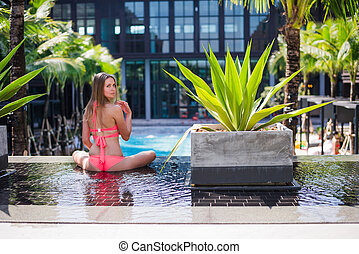 An attractive young woman doing yoga beside the swimming...