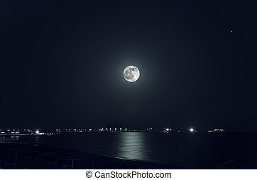 A beautiful night landscape of full moon over dark water...