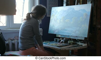 woman paints picture on canvas with oil paints in her studio 4k