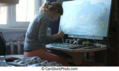 woman paints picture on canvas with oil paints in her studio...
