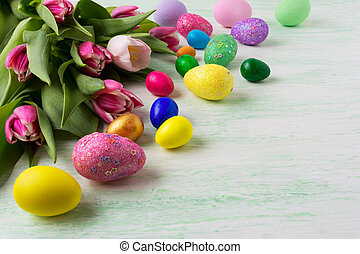 Easter hand painted eggs background with red tulips. Happy...
