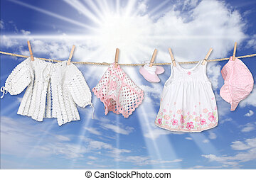 Baby Girl Clothing Hanging on a Clothesline Outdoors -...