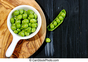 Green Peas in a container on a board with copy space