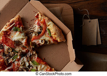 pizza in cardboard pizza box - round slices of pizza on...